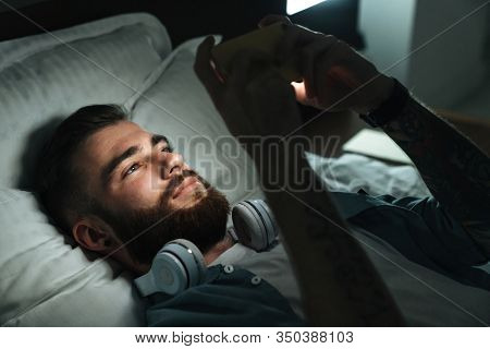 Smiling young bearded man laying on bed at home at night, using mobile phone