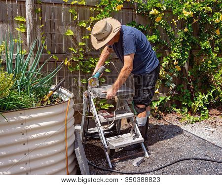 Male Retiree Cutting Stone To Pave His Backyard As A Weekend Project