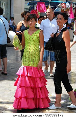 Malaga, Spain - August 18, 2008 - Young Woman In A Flamenco Dress Along Calle Marques De Larios At T