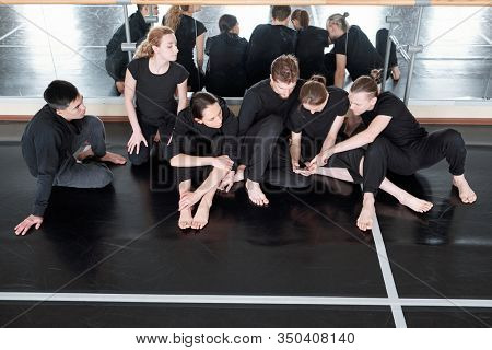 Contemporary dance teammates sitting together on floor against mirrors discussing something during break, high angle shot