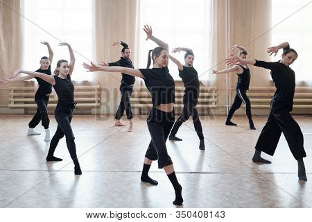 Horizontal shot of contemporary dance team learning new movements in their rehearsal moves