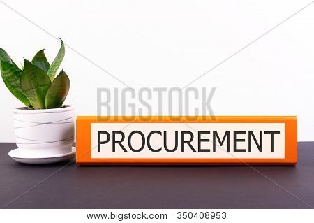 Procurement Inscription On An Office Folder Lying On A Dark Table With A Flowerpot And Flower On A L