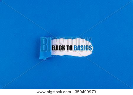 The Text Back To Basics Appearing Behind Torn Blue Paper.