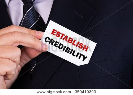 Businessman Putting A Card With Text Establish Credibility In The Pocket