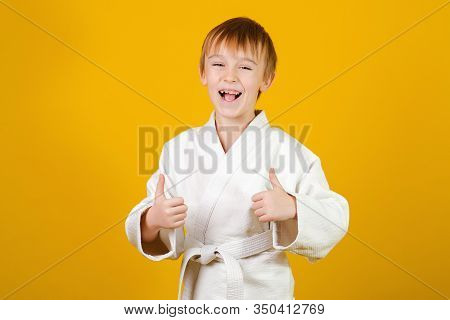 Smiling Happy Boy In A White Kimono. Sporty Kid On A Yellow Background. Martial Arts Concept. Sports
