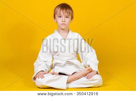 Serious Boy In A White Kimono Sitting On A Yellow Background. Martial Arts Concept. Little Boy Sitti