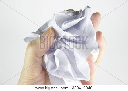 A Woman's Hand Holds A Crumpled Paper Ball With A Copy Of Space On A Gray Background. Crumpled Paper