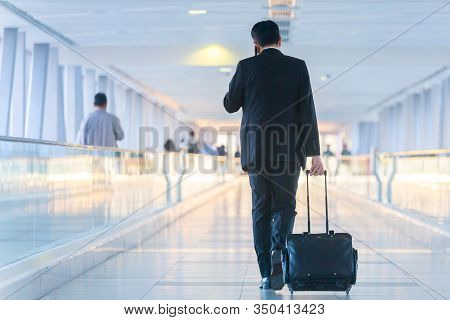 Businessman Walking And Wheeling A Trolley Suitcase At The Lobby, Talking On A Mobile Phone. Busines