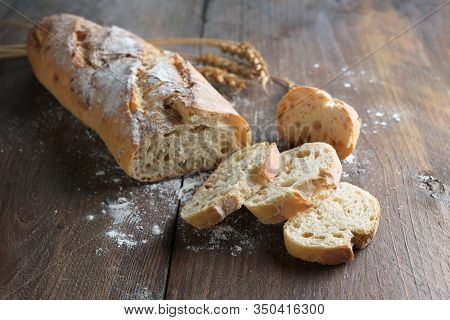 Half Sliced Baguette Or French Bread Baked With Onions On Dark Rustic Wood, Selected Focus, Narrow D
