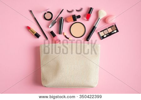 Makeup Bag With Cosmetic Products Spilling Out On To Pastel Pink Background. Flat Lay, Top View. Gla