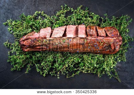Barbecued dry aged venison tenderloin fillet steak and saddle natural with herbs offered as top view on a rustic board