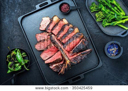 Barbecue dry aged wagyu porterhouse beef steak sliced with large fillet piece with hot chili and rapini broccoli rabe as top view on a modern design black cast iron tray with copy space