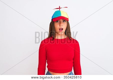 Young beautiful girl wearing fanny cap with propeller standing over isolated white background afraid and shocked with surprise expression, fear and excited face.