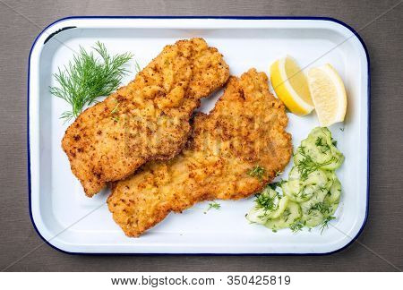 Traditional deep fried Wiener schnitzel from veal topside with cucumber salad and lemon slices offered as top view on a white tray