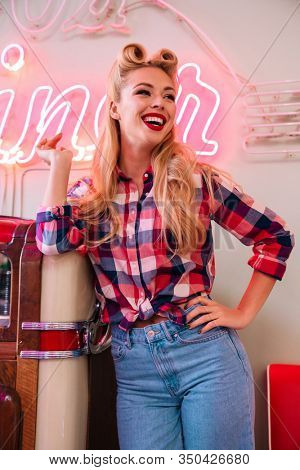 Photo of young joyful woman with beautiful hairstyle smiling while leaning jukebox in retro american cafe