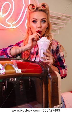 Photo of young pleased woman with beautiful hairstyle drinking milkshake while leaning jukebox in retro american cafe