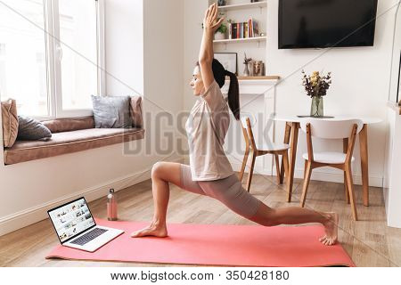 Image of a pretty young brunette fitness woman make stretching exercises indoors at home near laptop computer.