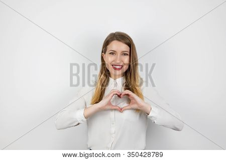 Young Blond Woman Making Heart Symbol With Her Hands Standing On Isolated White Background, Body Lan