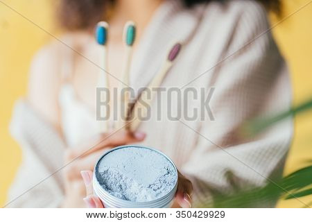 Close Up Of African American Girl Holding Three Bamboo Toothbrushes, Jar Of Tooth Powder On Yellow B