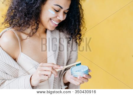 Young Beautiful Girl Holding A Useful Bamboo Toothbrush And A Jar Of Tooth Powder. The Concept Of A