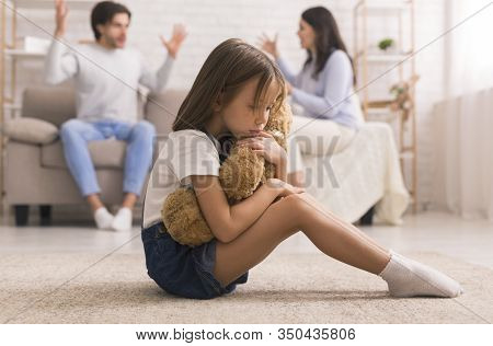 Family Problems. Cute Little Girl Suffering From Parents Arguing, Sitting On Floor With Teddy Bear,