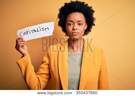 African American afro businesswoman with curly hair holding paper with capitalism message with a confident expression on smart face thinking serious