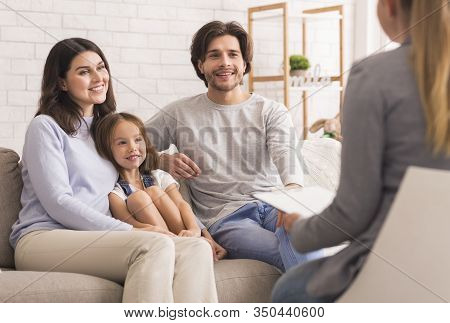 Happy Parents With Little Daughter Sitting Together At Psycholigists Office After Successful Family
