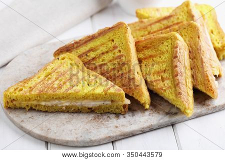 Grilled sandwiches with ham and cheese on a marble cutting board. Toast bread with curcuma gives a bright yellow color