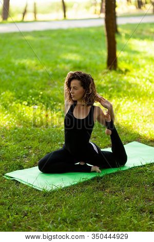 Beautiful Smiling Woman In Morning Park Doing Yoga And Outdoor Gymnastics. Green Grass And Rays Of S