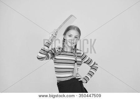 Haircare Begins With Combing. Little Child Hold Hair Comb Yellow Background. Haircare And Combing. H