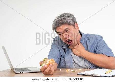 Asian Man Working And Eating A Burger On Office Desk And Holding His Neck After Choking Foods. Conce