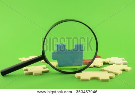 Colorful Jigsaw Puzzle Pieces With Magnifying Glass Focused On A Single Blue Corner Piece In A Conce