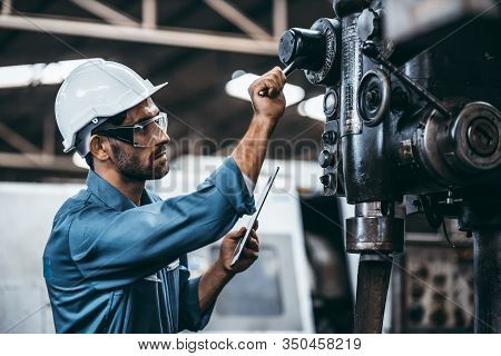 Engineer Working At Industrial Machinery In Factory. Manual Workers Cooperating While Measuring A El