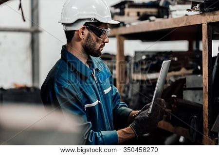 Adult Foreman Working On Digital Laptop In Aluminum Mill. Engineer Reading And Check A Plan On A Lap