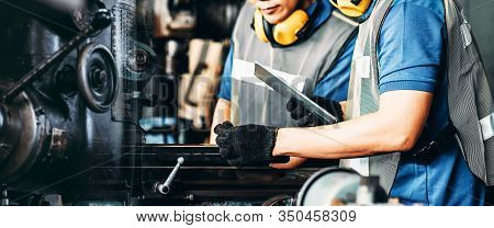Image Motion Engineer Working At Industrial Machinery In Factory. Manual Workers Cooperating While A