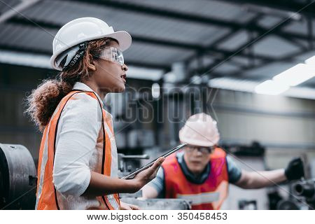 Female Industrial Engineer Wearing A White Helmet While Standing In A Heavy Industrial Factory Behin