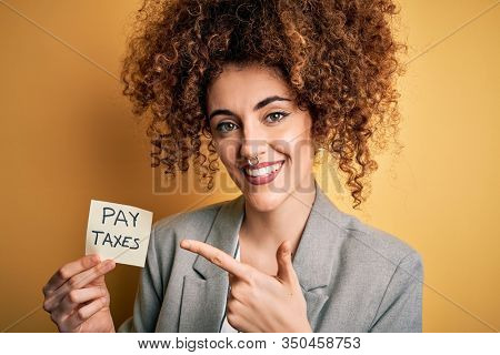 Young business woman with curly hair holding pay taxes to goverment reminder over yellow background very happy pointing with hand and finger