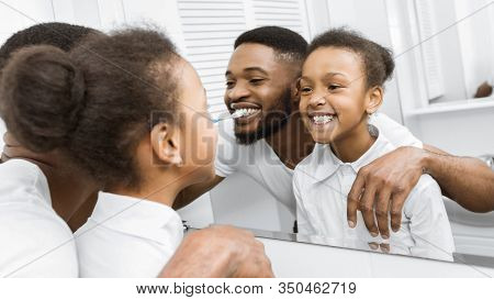 Morning Routine. Afro Girl And Father Brushing Teeth Together , Looking At Mirror, Panorama