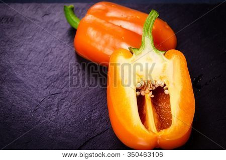 Orange Sweet Bell Pepper Cut In Half, Half Closeup With Seeds On A Dark Background. Place For Text,