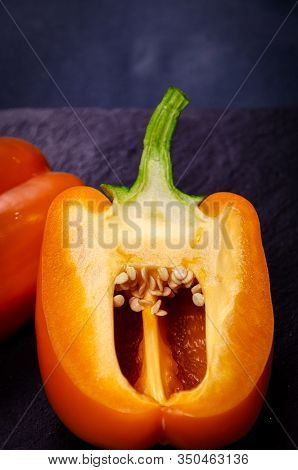 Orange Sweet Bell Pepper Cut In Half, Half Closeup With Seeds On A Dark Background, Agriculture.cuta