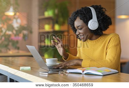 Afro Girl In Headset Using Laptop At Cafe, Having Skype Conference, Free Space