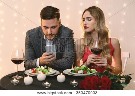 Cheating And Infidelity Concept. Curious Young Woman Peeking Into Boyfriends Smartphone During Roman