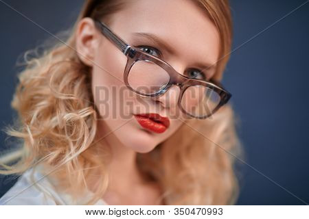 Studio portrait of a fashionable blonde woman in elegant glasses. Optics, eyewear. Copy space.