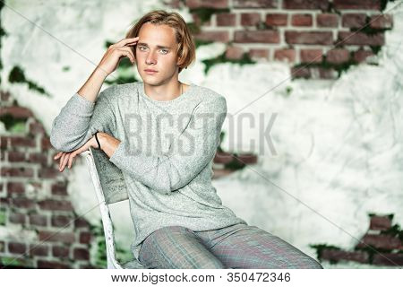 A portrait of a young goodlooking man sitting on the chair. Casual men fashion.
