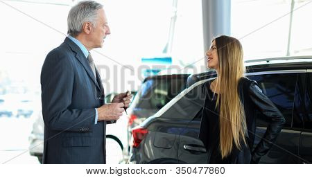 Portrait of a car salesman giving car keys to young woman standing next to white shiny luxury car in dealership showroom