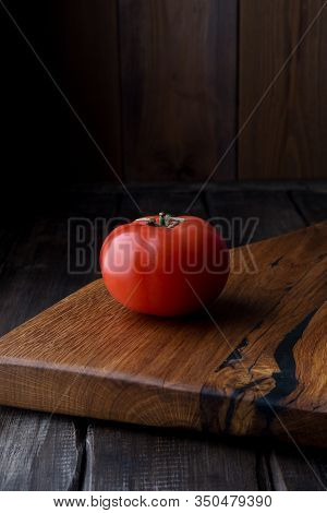 Tomato At Wood Board, Dark Mood. One Whole Fresh Red Tomato At Wooden Table. Concept Of Healthy Food