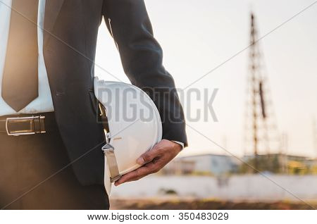 Engineer Or Safety Officer Holding Hard Hat With The Crane Background In Construction Site.