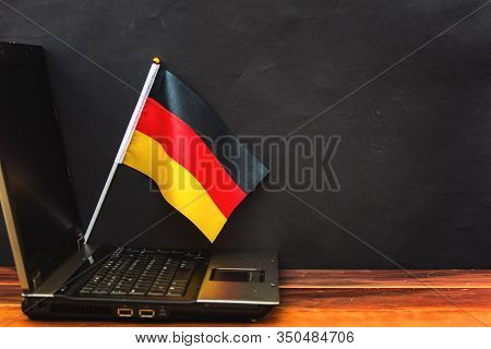 Flag Of Germany , Computer, Laptop On Table And Dark Background