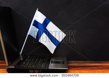 Flag Of Finland , Computer, Laptop On Table And Dark Background