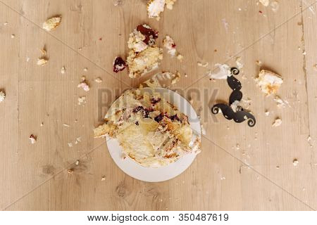 Smashed First Birthday Cake On Floor Flat Lay Photo. Destroyed Delicious Creamy Celebrate Biscuit De